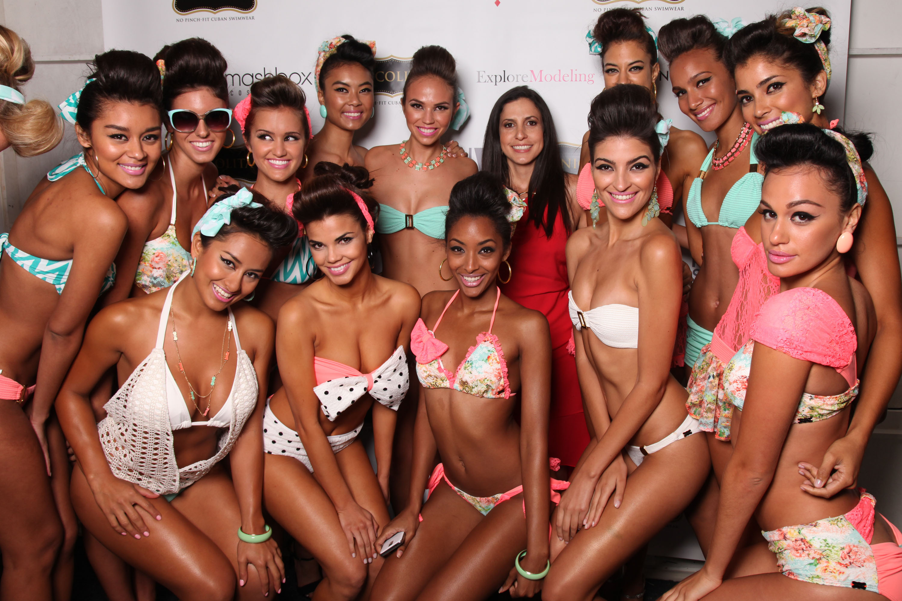 Designer Nicole Di Rocco, center in red, poses with her models backstage after the Nicolita runway show on Day 3 of Mercedes-Benz Fashion Week Swim 2014 at The Raleigh Hotel on Saturday, July 20, 2013 in Miami Beach, FL. (Photo by Omar Vega/Invision/AP Images)